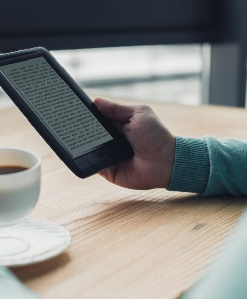 cropped view of man holding cup of tea near e-reader while studing at home